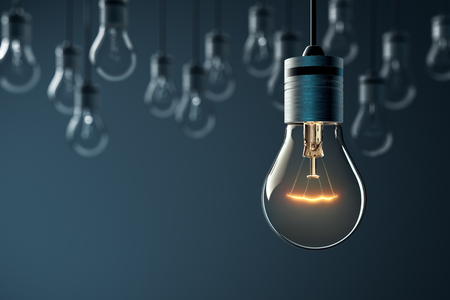 concept and ideas: Hanging glowing light bulb on blue background
