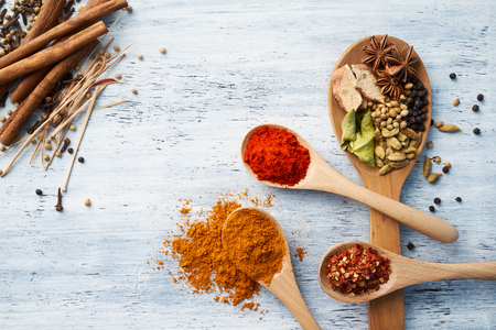 crushed red peppers: Wooden spoon filled with herbs and spices on white painted table