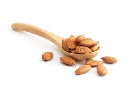 Almonds on wooden spoon isolated over white background