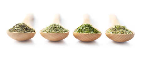 dried herbs: Wooden spoon filled with dried herbs on white background