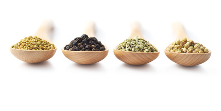 black peppercorn: Wooden spoon filled with spices - fenugreek, black peppercorn, fennel and coriander Stock Photo