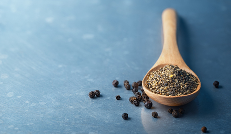 ground: Wooden spoon filled with ground pepper and Black Peppercorns Stock Photo