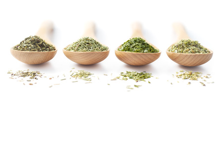 Wooden spoon filled with dried herbs on white background