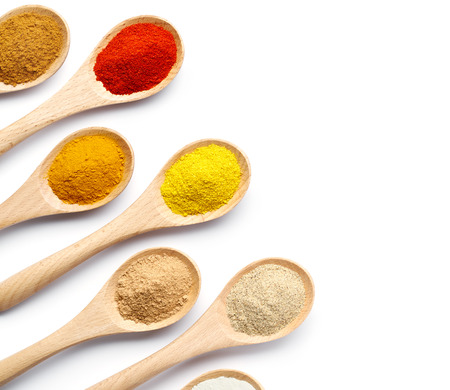 Spoon filled with colorful spices on white background