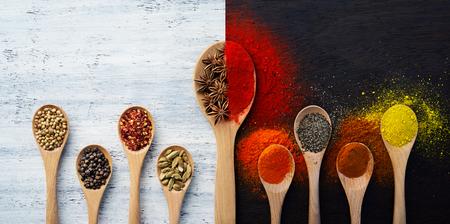 especias: Cuchara de madera llena de especias, hierbas, polvos y especias molidas