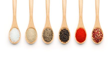 pepe nero: Cucchiaio di legno riempito con varie spezie su sfondo bianco