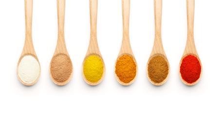 especias: Cuchara de madera llena de especias de colores sobre fondo blanco