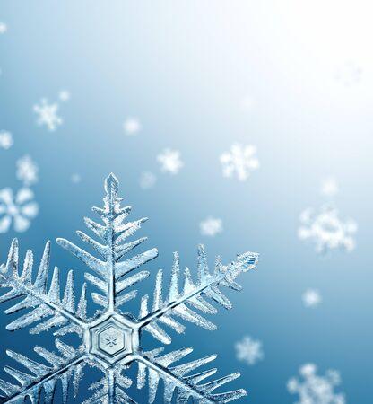 Macro sneeuwvlok en gevallen defocused sneeuwvlokken op blauwe achtergrond Stockfoto