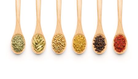 cuchara: Cuchara de madera llena de diversas especias en el fondo blanco