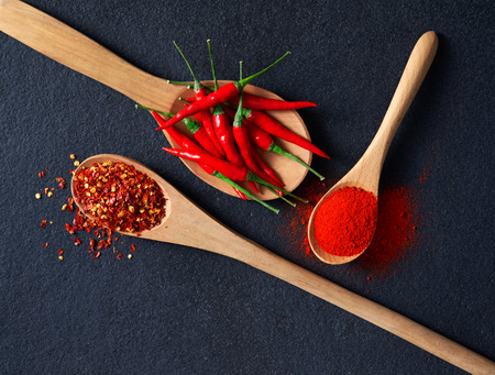 Wooden spoon filled with Chilli, Red Pepper Flakes and Chilli Powder Stockfoto