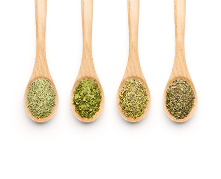 dried herbs: Wooden Spoon filled with herbs on white background