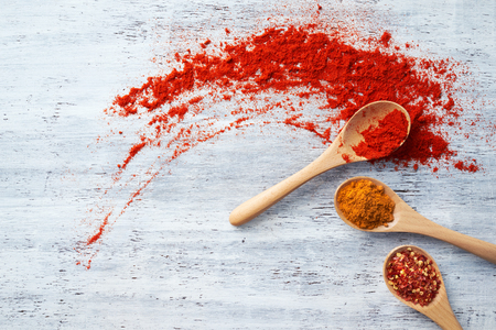 crushed red peppers: Wooden spoon filled with spices on white painted table