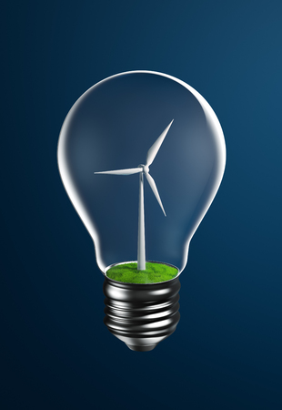 electricity generation: Wind turbine on grassland inside a light bulb representing clean energy Stock Photo