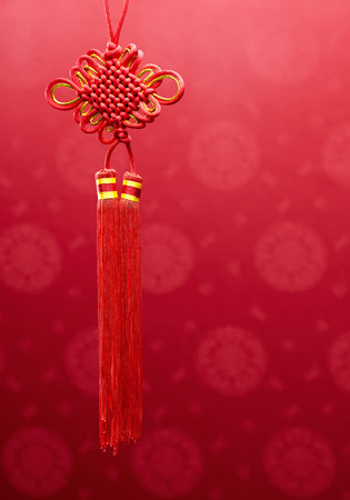 Chinese knot hanging decoration over red fabric with oriental motifs background