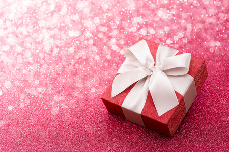Red gift box with white bow on pink glitter background Foto de archivo
