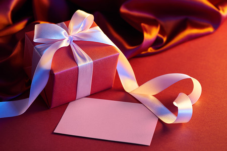 Gift box with heart shape ribbon on red background