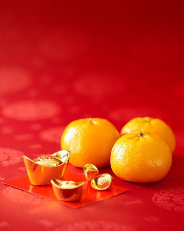 Chinese New Year - Mandarin orange, gold sycee (Foreign text means wealth) and red packet Stock Photo - 50799736