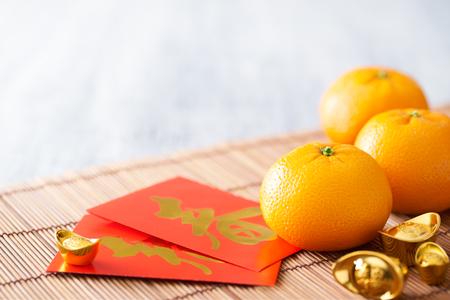 중국 설날은 - 만다린 오렌지, 골드 sycee 흰색 페인트 나무 테이블에와 빨간 패킷 (외국인 텍스트가 봄 시즌을 의미) (외국인 텍스트는 재산을 의미)