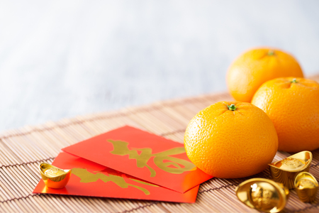 Chinees Nieuwjaar - Mandarijn sinaasappel, goud sycee (Buitenlandse tekst betekent rijkdom) en rode pakje (Buitenlandse tekst betekent voorjaar) op wit geschilderde houten tafel Stockfoto