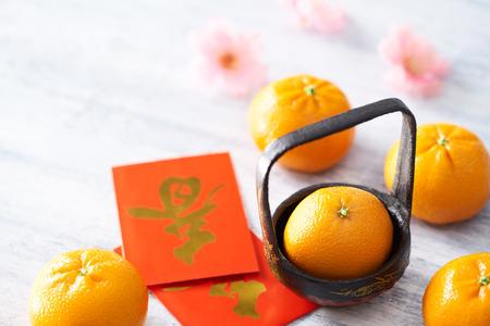 Chinees Nieuwjaar - Mandarin oranje en rood pakje (Buitenlandse tekst betekent voorjaar) op wit geschilderde houten tafel Stockfoto