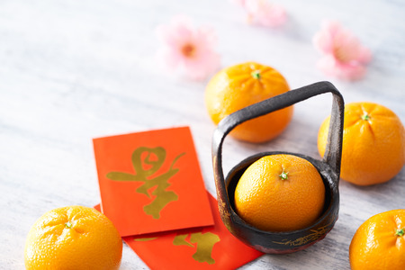 Chinese New Year - Mandarin orange and red packet (Foreign text means spring season) on white painted wood table