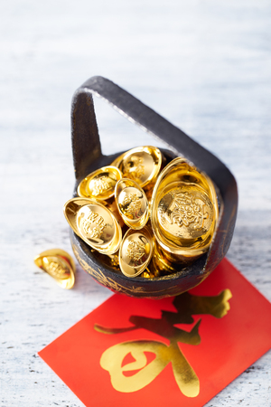red packet: Chinese New Year - Gold sycee (Foreign text means wealth) and red packet (Foreign text means spring season) on white painted wood table