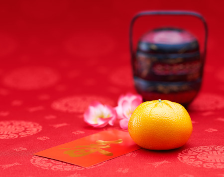 chinese tradition: Chinese New Year - Mandarin orange and red packet (Foreign text means spring season)