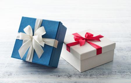 Blauwe en witte geschenkdoos met lint op wit geschilderde houten achtergrond