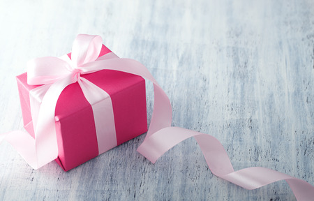 her: Pink gift box with ribbon on white painted wood background