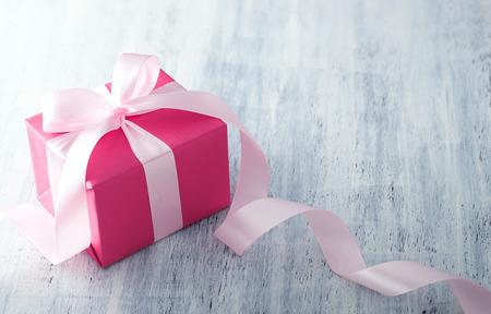 pink: Rosa Geschenk-Box mit Band auf weißem lackiertem Holz Hintergrund