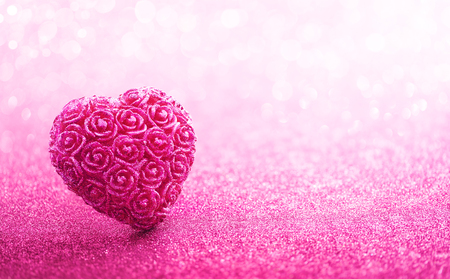 romantic love: Glittering heart shaped with rose craft over pink bokeh background