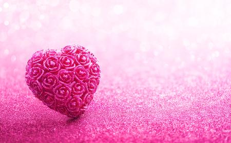 anniversario matrimonio: Scintillanti a forma di cuore con il mestiere rosa su sfondo rosa bokeh Archivio Fotografico