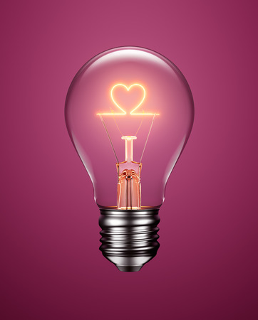 Light bulb with filament forming a heart icon on purple background Foto de archivo