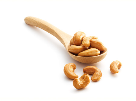 Roasted Cashew Nuts on wooden spoon isolated over white background