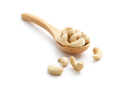 Cashew Nuts on wooden spoon isolated over white background
