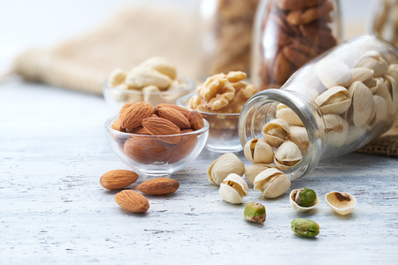 painted background: Healthy nuts on white painted wood background Stock Photo