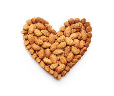 forme: Almond nuts formant une forme de coeur isolé sur blanc Banque d'images