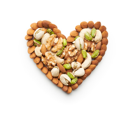 almond: Mixed nuts forming a heart-shape isolated on white Stock Photo