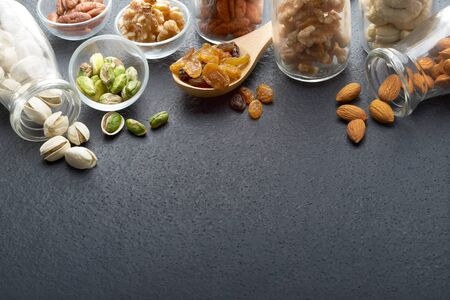 Nuts and dried food on slate background with copy space