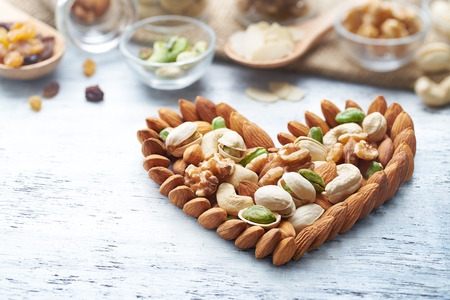 Mixed nuts forming a heart-shape on white painted wood background 스톡 콘텐츠