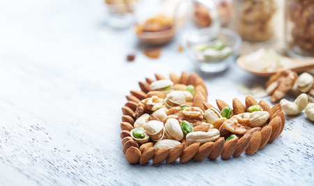 painted background: Mixed nuts forming a heart-shape on white painted wood background Stock Photo
