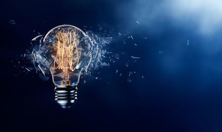 bombillas: La explosión de la bombilla en un fondo azul Foto de archivo