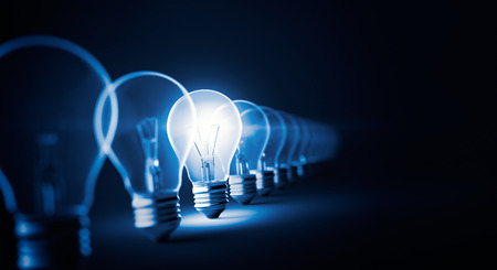 Glowing light bulb on dark blue background