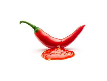 Chili sauce leaking from a chili pepper cut isolated on white background