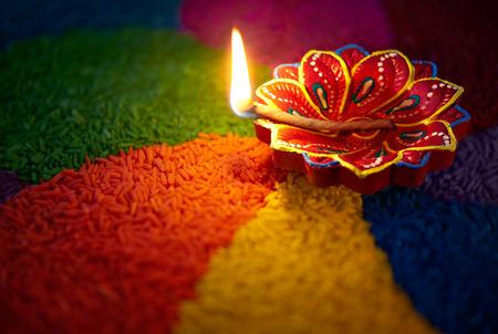 lit lamp: Diwali oil lamp - Diya lamp lit on colorful rangoli