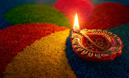 Diwali oil lamp - Diya lamp lit on colorful rangoli
