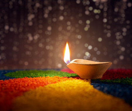 Traditional diya lamp lit on colorful rangoli Stock Photo