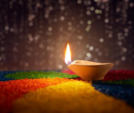 Traditional diya lamp lit on colorful rangoli Standard-Bild