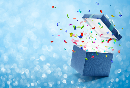 Confetti popping out from blue gift box - bokeh background Stockfoto