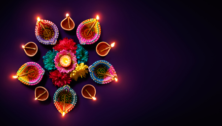Colorful clay diya lamps with flowers on purple background